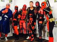 ryan reynolds poses with deadpool cosplayers